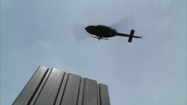 ws military helicopter hovering close to upper floors of high rise modern office building - helicopter rotors stock videos and b-roll footage