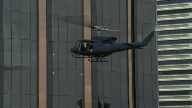 WS Military helicopter hovering close to upper floors of high rise modern office building