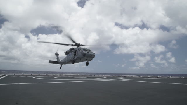 military helicopter landing on aircraft carrier, wide shot montage - helicopter landing stock videos & royalty-free footage