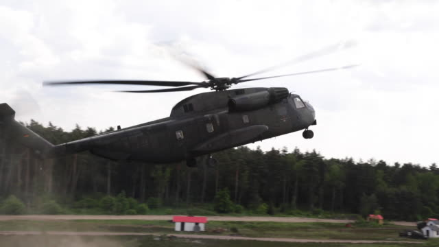 military helicopter lands in rural germany, pan right - propeller stock videos & royalty-free footage