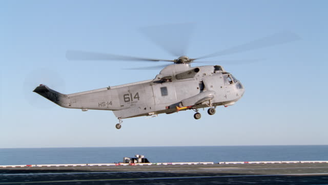 a military helicopter lands on an aircraft carrier. - helicopter landing stock videos & royalty-free footage