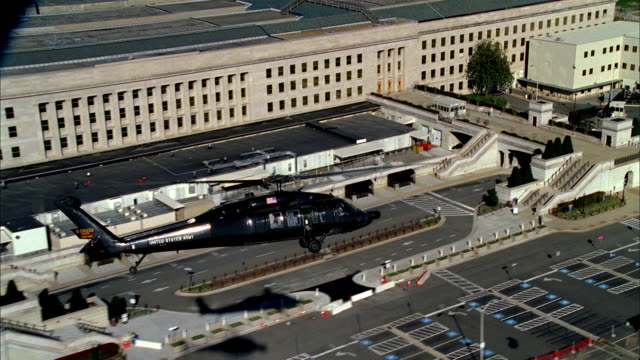 vidéos et rushes de a military helicopter patrols over the pentagon in washington, d.c.. - pentagone arlington