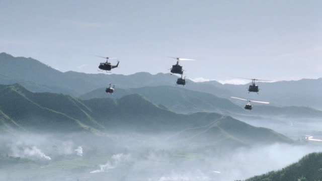 military helicopters fly over misty valleys and mountain ranges in vietnam. - vietnam war stock videos & royalty-free footage