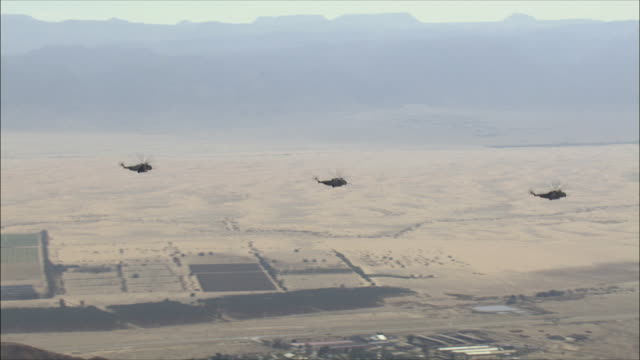 AERIAL WS PAN Military helicopters flying over desert, Arava, Israel