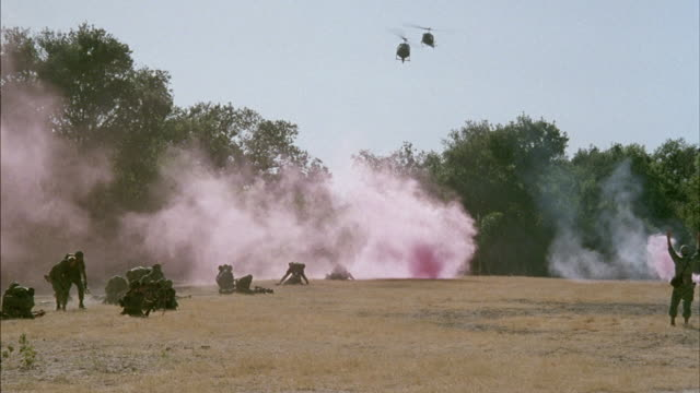 Military helicopters pick up wounded soldiers from a field.