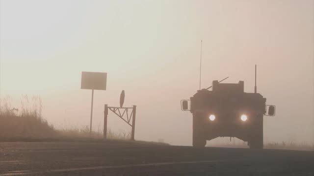 a military hummer travels down a road towards camera - hummer stock videos and b-roll footage