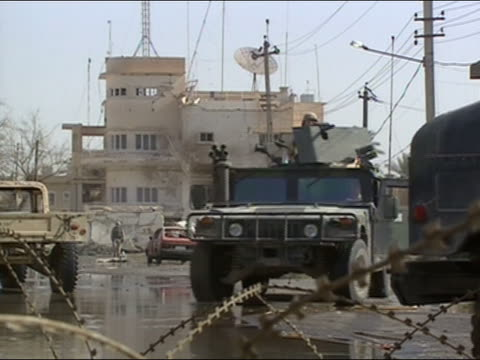 US military Humvee driving toward CAM with bombdamaged building / barbed wire in foreground / Baghdad