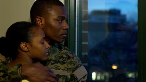 vidéos et rushes de mari militaire et épous'étreinte près de la fenêtre - armée américaine