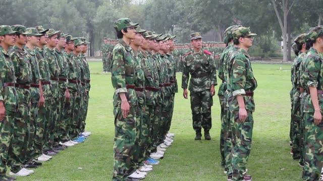 A military instructor walks around rows of soldiers during training.