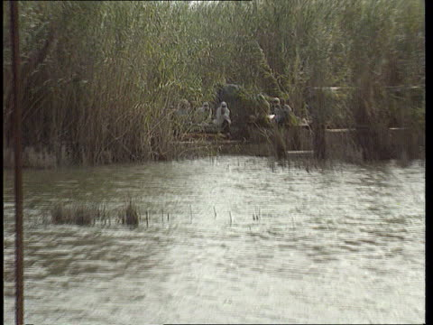 Bosnia/Iraq IRAQ LMS Marsh arabs sitting amongst reeds PULL OUT others sitting on platforms by river LMS Shia arab along in boat along river LMS Arab...