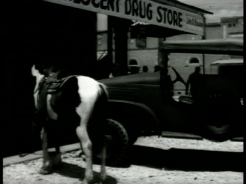 vidéos et rushes de military jeep parked w/ horse at drug store vs army service men in uniform congregating on streets walking getting shoe shined by young boy lifestyle - 1941