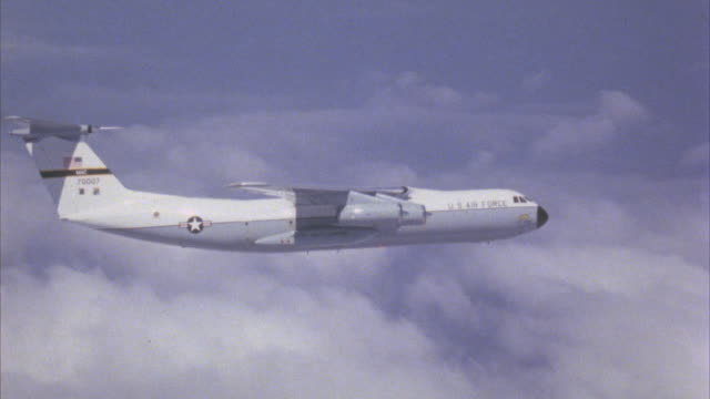 air to air, military jet flying above clouds  - 1971 stock-videos und b-roll-filmmaterial