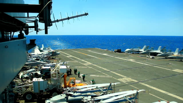 Military jet landing on  Aircraft Carrier.