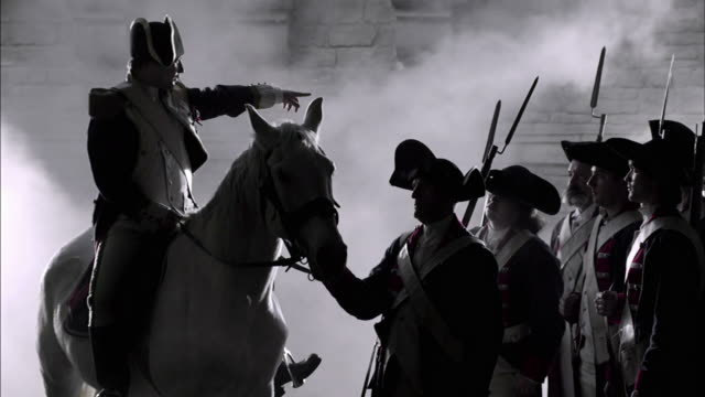 a military leader on a white horse gives orders to soldiers in french revolution uniforms. - historische nachstellung stock-videos und b-roll-filmmaterial
