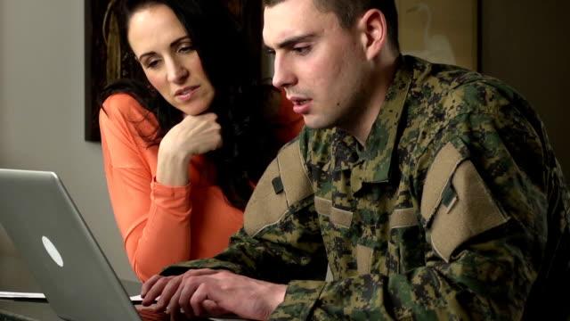 militärische mann und frau kontakt mit laptop-computer - wohngebäude innenansicht stock-videos und b-roll-filmmaterial