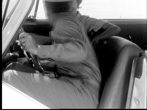 vidéos et rushes de 1955 film montage ms military man sitting down in driver's seat of car and kissing woman on other side/ cu man fastening seatbelt - ceinture de sécurité
