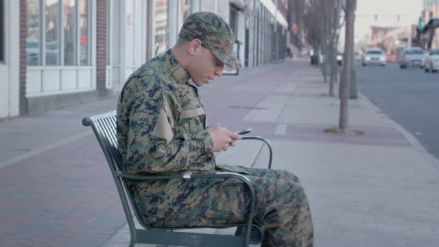 Military Man Texting in an Urban Setting