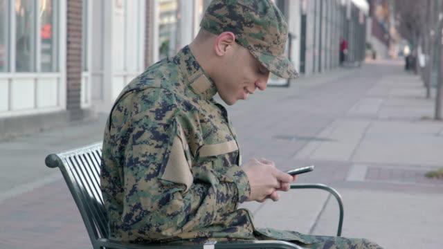 mann des militärs sms in einem städtischen umfeld - soldat stock-videos und b-roll-filmmaterial