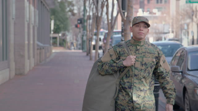 Military Man Walks on Urban Street Setting