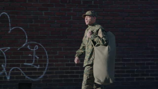 vídeos y material grabado en eventos de stock de hombre militar camina sobre el entorno urbano calle - perfil vista de costado
