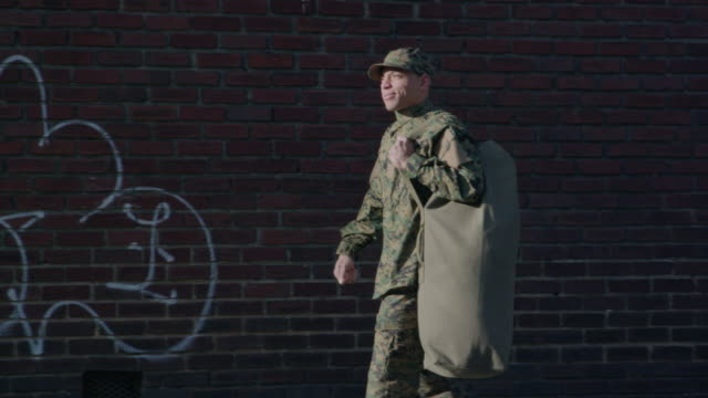 military man walks on urban street setting - war veteran stock videos & royalty-free footage