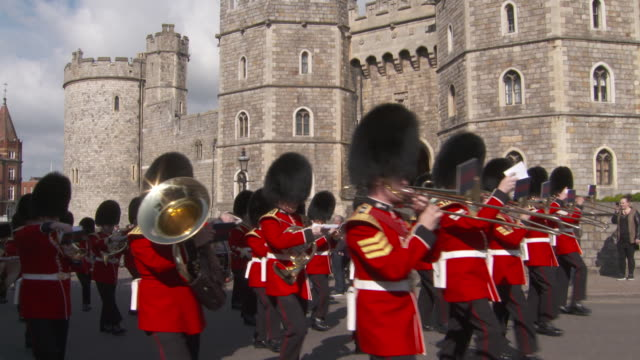 a military marching band plays as it passes windsor castle in whose chapel prince harry and meghan markle plan to marry in spring 2018 uk fkau104l... - windsor england stock videos and b-roll footage