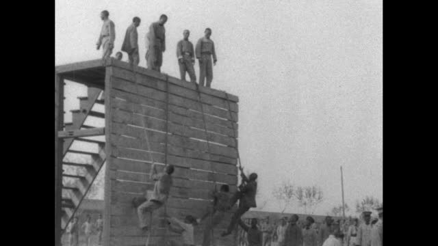 military men in training climb a vertical wooden wall and jump from it / note exact month/day not known - military camp stock videos & royalty-free footage
