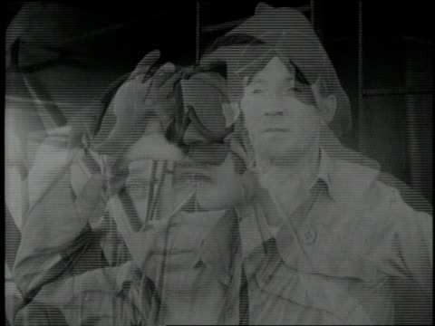 military men put on goggles to observe the testing of an atomic weapon. - skibrille stock-videos und b-roll-filmmaterial