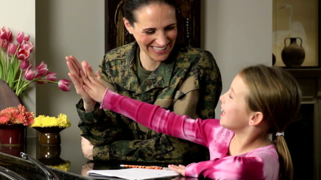 military mom helps daughter with homework - marines stock videos & royalty-free footage
