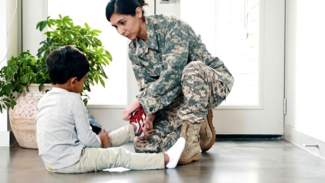 military mom teaches son to put on his shoes - armed forces stock videos & royalty-free footage