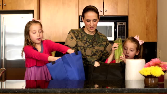 militärische mutter mit ihrer tochter unloads lebensmittel - wohngebäude innenansicht stock-videos und b-roll-filmmaterial