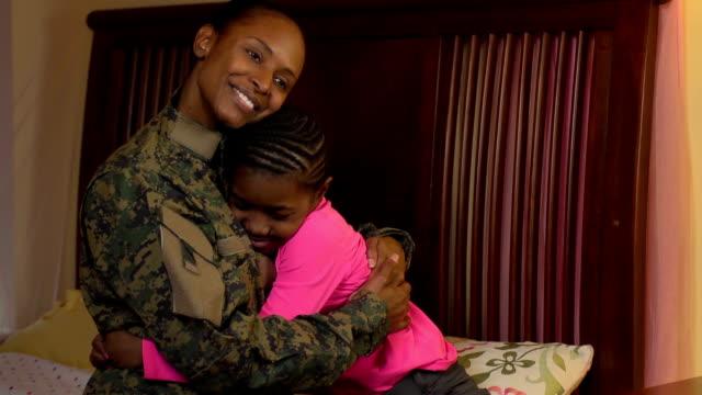 Militärische Mutter umarmt ihre Tochter