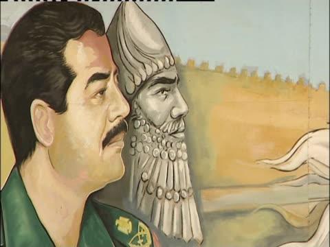 A military mural displaying Saddam Hussein covers a billboard in Iraq.