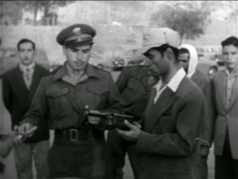1957 military officer demonstrating rifle to men outdoors / Syria / newsreel