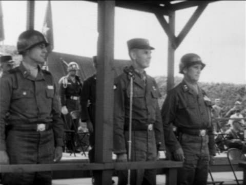 us military officers standing at attention watching something offscreen / end of korean war - 1953年点の映像素材/bロール
