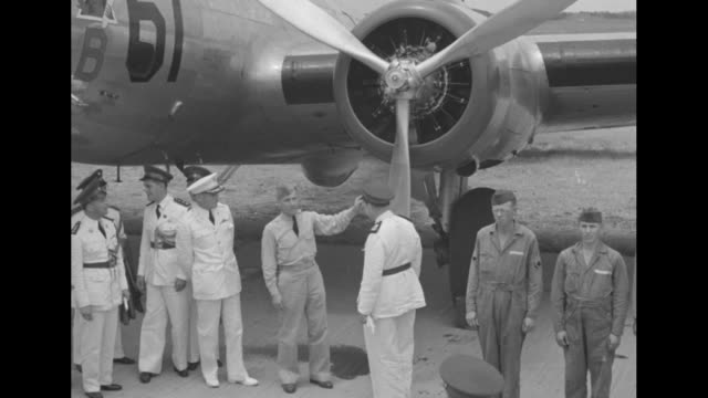 Military officers' troop review of scores of soldier with a row of airplanes behind them / Major Harold L George explains propeller assembly of a...