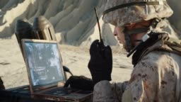 Military Operation in the Desert, Using Satellite or Drone Technology: Soldier with Laptop Monitors Movement of Armed Terrorist Vehicle, Uses Radio Communication to Call an Air Strike.