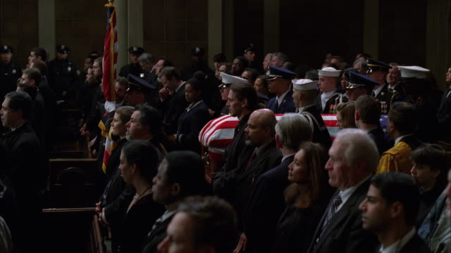 Military pall bearers carry a coffin past filled pews.