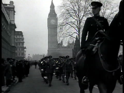 Military parade being led by officer on horseback followed by band men in uniform Parliament clock tower BG WS Soldiers walking in narrow parade...