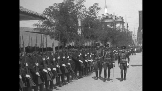 vídeos de stock, filmes e b-roll de military parade in the 1910s possibly the russian army officers march down street to soldiers in rows with rifles with bayonets / military band... - uniforme militar