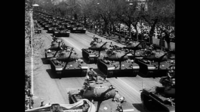 stockvideo's en b-roll-footage met / military parade to celebrate end of spanish civil war / tanks roll down the streets and military planes fly overhead / francisco franco and his... - 1957
