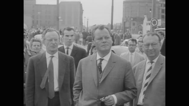 military personnel and vehicles gather at brandenburg gate as west berliners and mayor willy brandt come out to watch - 1961 stock-videos und b-roll-filmmaterial