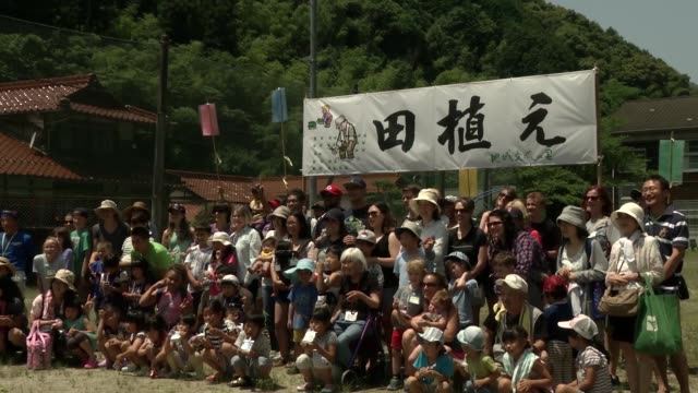 us military personnel based at iwakuni take part in community rice planting in a rice paddy - 麦わら帽子点の映像素材/bロール