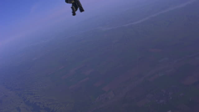 A military pilot jumping off from an airplane while strapped to an ejection seat.