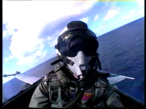 CU, Military pilot wearing helmet and mask taking off from deck of aircraft carrier