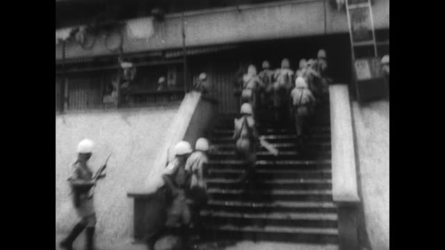 vidéos et rushes de military police disembark from bus / police run up the steps of a building / protestors stand on multistorey balconies in protest / police officer... - 1967