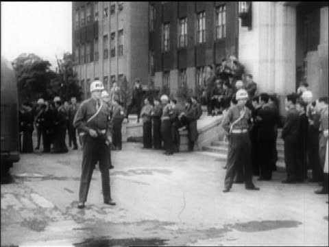 vidéos et rushes de b/w 1945 military police guarding building in tokyo / crowd in background / newsreel - 1945