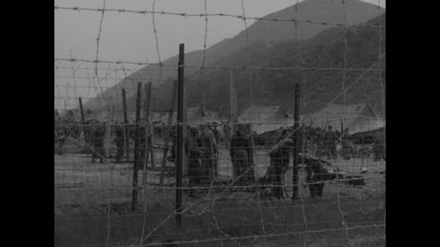 military police walk in geoje-do pow camp, escorting some pows; one mp carries rolled-up flags on small poles / pows board truck / driver and black... - mp stock-videos und b-roll-filmmaterial