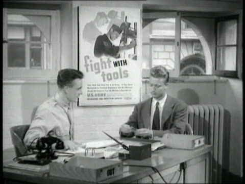 military recruiting officer at a desk shows a document to a man in a suit. - military recruit stock videos & royalty-free footage