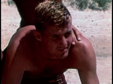 stockvideo's en b-roll-footage met 1968 montage military recruitment film with a woman taking a picture of a group of men doing a pyramid in the sand then falling down when another woman in a car drives up to pick up the woman / united states  - military recruit